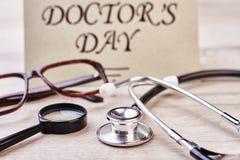 Loupe, stetoskop och hälsningkort Arkivfoton