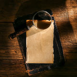 Loupe sur la feuille antique de papier parcheminé sur le livre Photo libre de droits