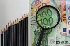 Loupe sur la pile d'euro billets de banque et crayons comme se levant Photo libre de droits