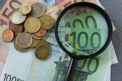 Loupe sur la pile d'euro billets de banque et pièces de monnaie comme affaires Photo stock