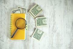 Loupe sur le bloc-notes avec l'argent photo libre de droits