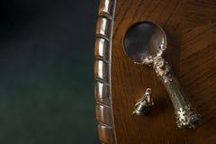 Loupenärbild, tappningförstoringsapparat som är handgjord på mörk trätabellbakgrund, begrepp av sökandet, utredning, privat krimi royaltyfria foton