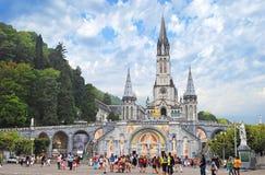 """LOURDES †""""AUGUSTI 23: Kristenkors på en bakgrund basilikan Fotografering för Bildbyråer"""
