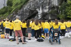 Detail of the assistants to the holy mass in Lourdes France. LOURDES, FRANCE - JULY 6, 2016: Details of those attending the Holy Mass, volunteers and pilgrims stock photography
