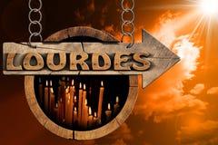 Lourdes - sinal com velas votivas no por do sol Imagem de Stock