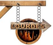 Lourdes - sinal de madeira com velas votivas Imagens de Stock Royalty Free