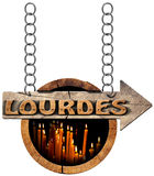 Lourdes - Wooden Sign with Votive Candles Stock Photo