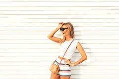Louro à moda bonito no short e nos óculos de sol, rindo emocionalmente para fora ruidosamente fotografia de stock