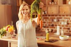 Louro alegre que demonstra a cenoura orgânica fotos de stock royalty free