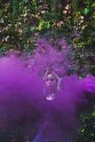 Louro atrás do fumo violeta, fora foto de stock