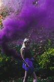 Louro atrás do fumo violeta, fora imagem de stock