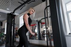 Louro atrativo da jovem mulher no sportswear que faz exercícios da força para as mãos com a ajuda do simulador moderno fotografia de stock royalty free