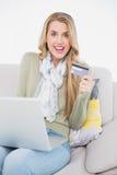 Louro bonito alegre que usa seu cartão de crédito para comprar em linha Fotografia de Stock