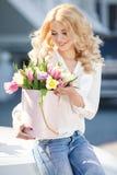 Louro bonito com as flores na caixa de presente foto de stock