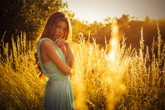 Louro bonito com um cabelo encaracolado longo em um vestido de noite longo no movimento fora na natureza no por do sol do verão Fotos de Stock Royalty Free