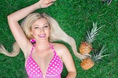 Louro bonito da jovem mulher em um biquini cor-de-rosa que encontra-se na grama com dois abacaxis foto de stock