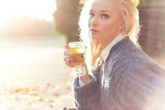 Louro bonito da menina no chá bebendo da camiseta morna no parque em um dia ensolarado do outono nos raios brilhantes do sol Imagem de Stock