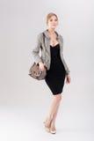 louro bonito da mulher de negócio no vestido, no revestimento e em purs pretos Fotos de Stock Royalty Free