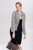 louro bonito da mulher de negócio no vestido, no revestimento e em purs pretos Imagens de Stock