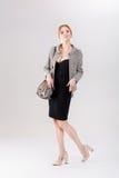 louro bonito da mulher de negócio no vestido, no revestimento e em purs pretos Fotografia de Stock Royalty Free