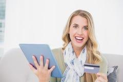 Louro bonito de sorriso que usa seu cartão de crédito para comprar em linha Fotografia de Stock