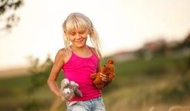 Louro bonito do bebê com brinquedos macios em um campo no verão imagens de stock