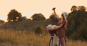 Louro bonito em um chapéu com uma bicicleta que olha a tela do telefone celular e uma cesta no guiador com flores video estoque