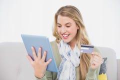 Louro bonito feliz que usa seu cartão de crédito para comprar em linha Foto de Stock Royalty Free