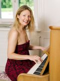 Louro bonito jogando o piano em casa Imagens de Stock