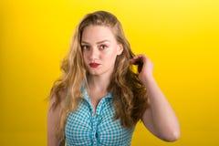 Louro bonito na camisa de algodão azul e branca em uma parte traseira do amarelo Fotos de Stock Royalty Free