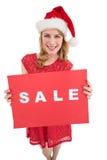 Louro bonito no chapéu de Santa que guarda um cartaz vermelho da venda Foto de Stock Royalty Free