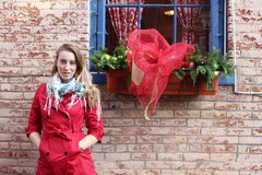 Louro bonito no revestimento vermelho contra a parede de tijolo Imagem de Stock