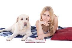 Louro bonito novo nos pijamas que encontram-se com o isolado do livro e do cão imagens de stock