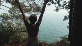 Louro caucasiano feliz novo joga acima suas mãos em um banco alto em um fundo azul do mar Slowmo filme