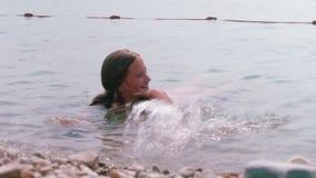 Louro caucasiano feliz novo que espirra no mar perto de uma costa rochosa video estoque