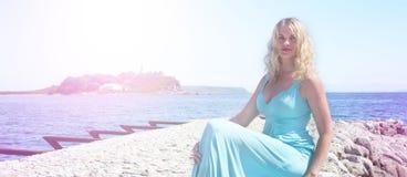 Louro da menina da bandeira que senta-se nas rochas no verão azul do horizonte da praia do sol do farol do céu do vestido do mar imagens de stock