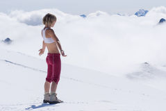 Louro da menina nas montanhas nevado altas acima das nuvens Fotografia de Stock