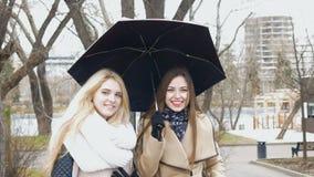 Louro de duas amigas e morena bonitos - estar de fala sob um guarda-chuva Dia ensolarado, os sopros do vento video estoque
