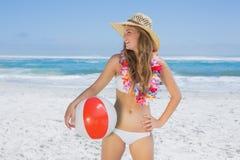 Louro de sorriso apto no chapéu branco do biquini e de palha que guarda a bola de praia fotografia de stock royalty free