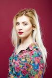 Louro de sorriso bonito com os bordos sensuais que vestem a camisa colorida no fundo cor-de-rosa Retrato de mulher surpreendente  Foto de Stock