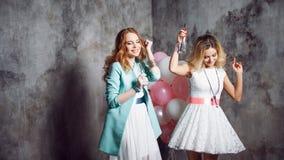 Louro e ruivo Duas amigas encantadores novas no partido com balões No fundo textured cinzento Fotos de Stock Royalty Free