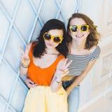 Louro elegante e morena das meninas dos pares novos bonitos em um vestido amarelo brilhante e nos óculos de sol que levantam e qu Foto de Stock Royalty Free