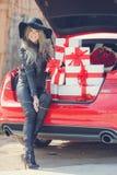 Louro elegante perto do carro com caixas de presente Imagem de Stock