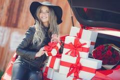 Louro elegante perto do carro com caixas de presente Foto de Stock