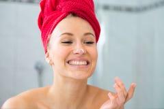 Louro em um banho com uma toalha vermelha na cabeça Imagens de Stock Royalty Free
