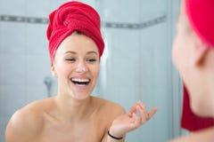 Louro em um banho com uma toalha vermelha na cabeça Fotos de Stock Royalty Free