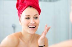 Louro em um banho com uma toalha vermelha na cabeça Fotografia de Stock Royalty Free