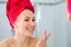 Louro em um banho com uma toalha vermelha na cabeça Fotos de Stock