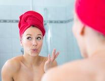 Louro em um banho com uma toalha vermelha na cabeça Foto de Stock Royalty Free