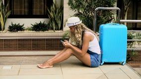 Louro em um chapéu, macacões com um saco azul, acordos da menina em um hotel tropical com uma piscina 4K filme